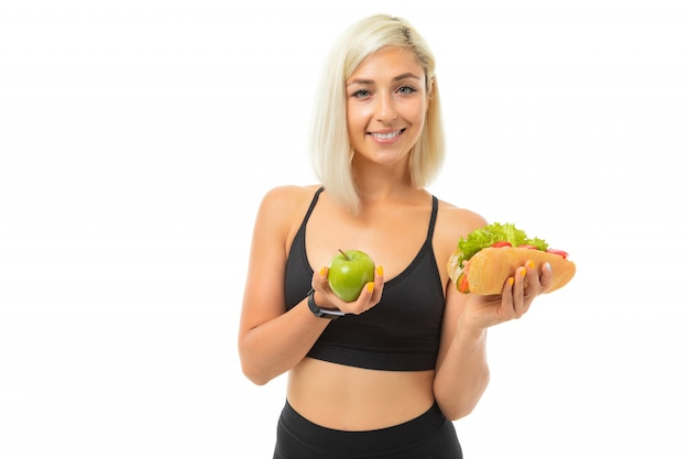 Sports girl in a sports uniform shows an apple and fast food on camera on white