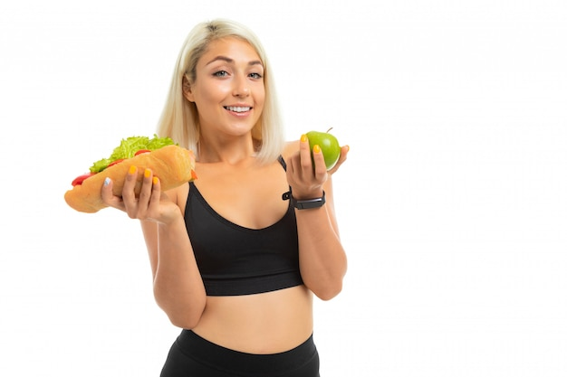 Sports girl in a sports uniform shows an apple and fast food on a camera