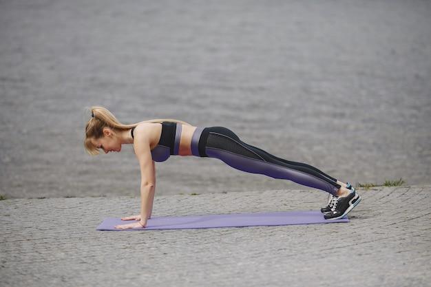 Спортивная тренировка девушки в летнем парке