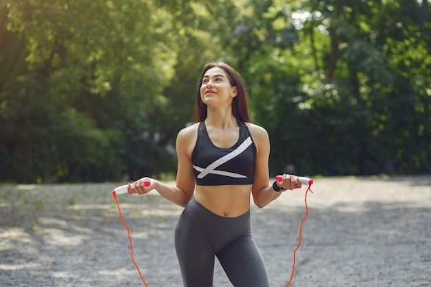 Sports girl training with jump rope in a summer park