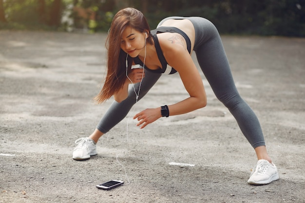 Sports girl training with phone and headphones
