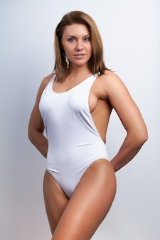 Sports girl in a white swimsuit on a white background