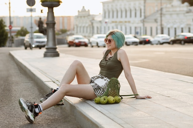 Sports girl with bag of fruit resting in summer in the city