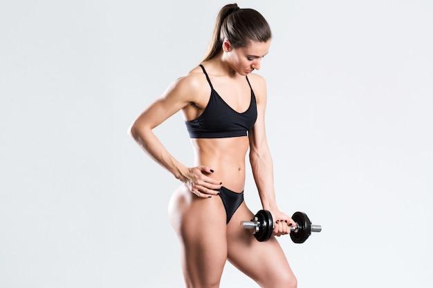 Спортивная девушка с гантелями на белом фоне. спорт, фитнес и упражнения.