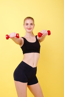 Sports girl with dumbbells on a yellow space