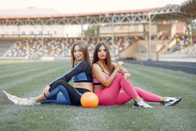Sports girls in a uniform training at the stadium