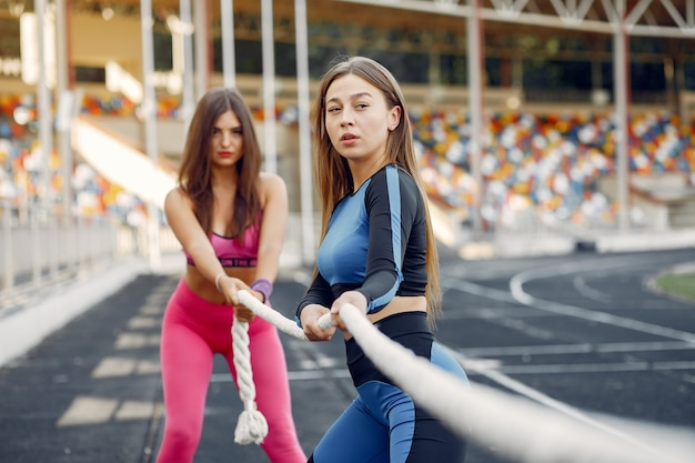Sports girls in a uniform training with rope at the stadium