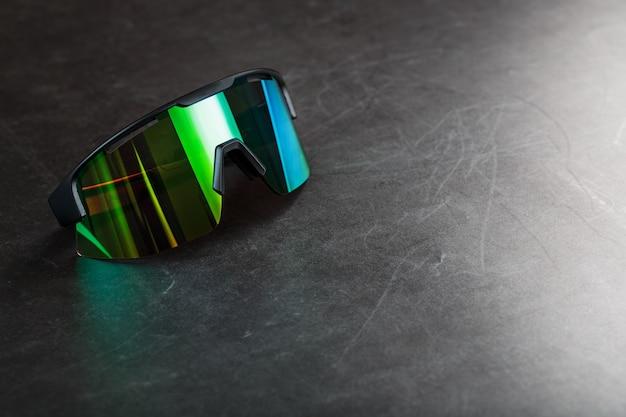 검은 질감 표면에 녹색 미러 렌즈가있는 스포츠 안경