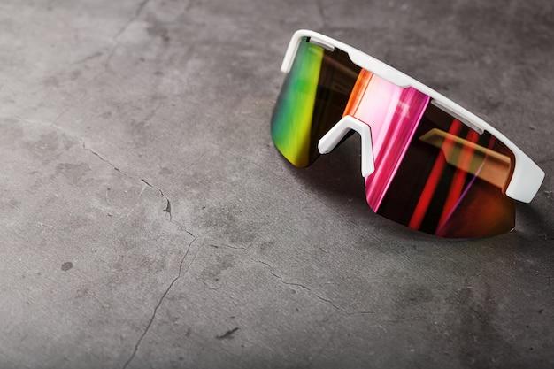 검은 색 표면에 빨간색 미러 렌즈와 흰색 프레임이있는 스포츠 안경
