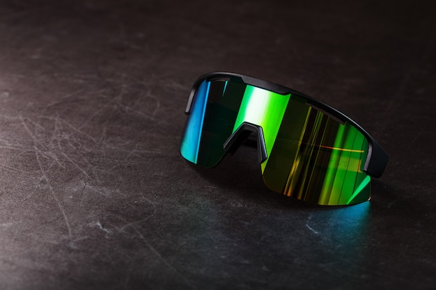 Sports glasses with a green mirrored lens and black frames on a black surface