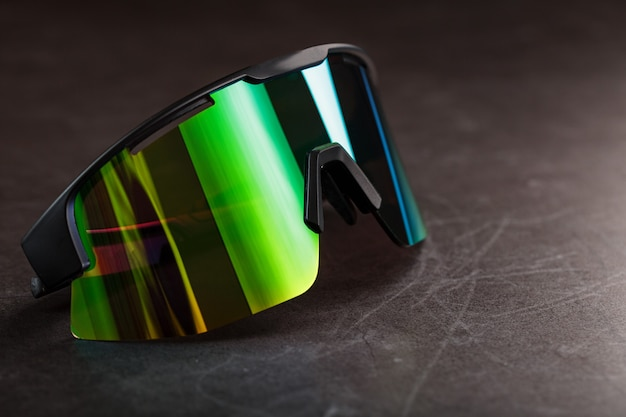 Sports glasses with a green mirrored lens on a black textured surface