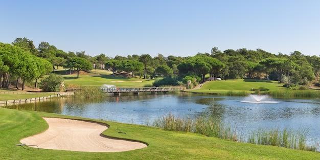 Спортивный гольф-парк в португалии. рядом озеро и фонтан.