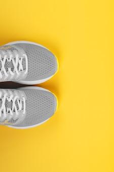 黄色の背景にスポーツグレーのスニーカー-スポーツコンセプト、フリースペース。 2021年の流行色は灰色と黄色の縦の構図です