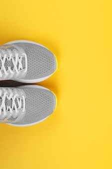 Sports gray sneakers on a yellow background - sport concept, free space. the trendy colors of 2021 are gray and yellow, vertical composition