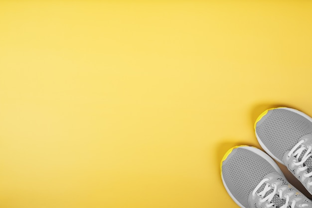 Sports gray sneakers on a yellow