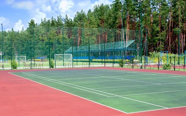 숲이 우거진 지역의 도시 외곽에 있는 운동장. 테니스 코트, 피트니스 장비, 축구장 및 기타 스포츠 팀 게임을 위한 공공 운동장의 전망.