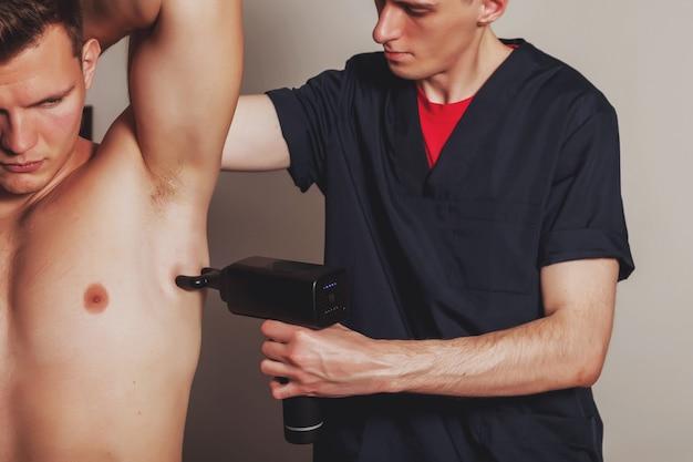 体育館の医療室でのスポーツガンパーカッションマッサージ。マッサージ師はホームマッサージの練習をします。スポーツボディのマッサージを再生するためのパーカッションセラピー。怪我のリハビリテーションの概念。コピースペース
