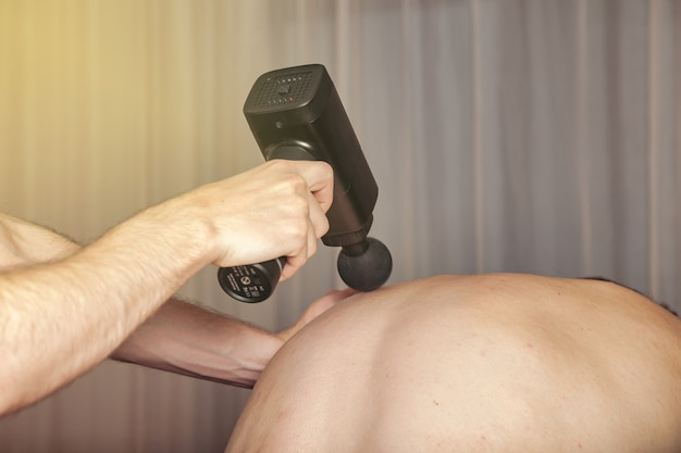 体育館の医療室でのスポーツガンパーカッションマッサージ。マッサージ師はホームマッサージの練習をします。スポーツボディのマッサージを再生するためのパーカッションセラピー。怪我のリハビリの概念。コピースペース