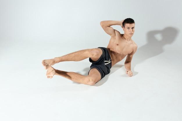 Спортивный парень делает упражнения в шортах в яркой комнате, вид спереди