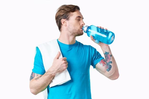 川の水のボトルとタトゥーの白い背景のフィットネスと青いtシャツのスポーツ男