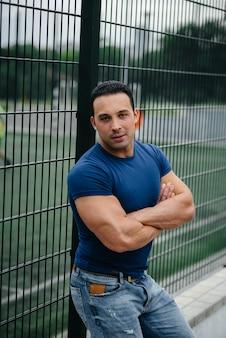 Спортивный парень стоит возле спортивной площадки. бодибилдинг.