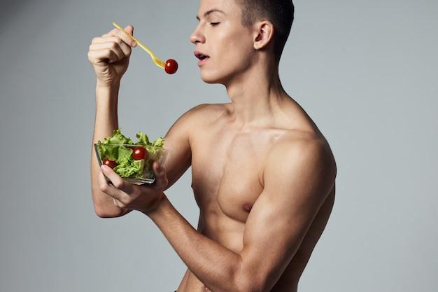 裸の胴体の健康的な食事野菜サラダエネルギートレーニングを持つスポーツ男