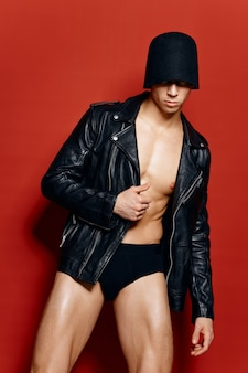 Спортивный парень с накачанным торсом и голыми ногами в черных трусиках в пиджаке-маске