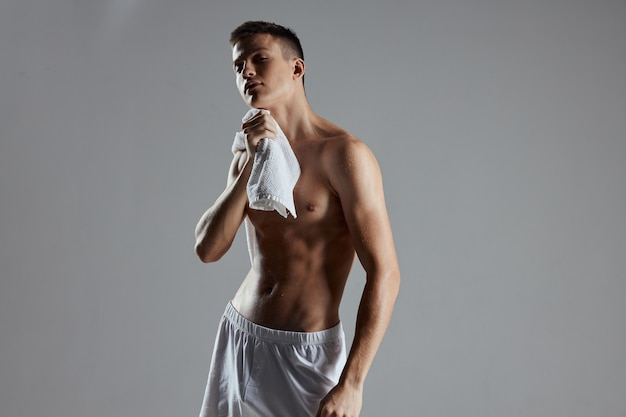 Sports guy with a naked torso white towel isolated