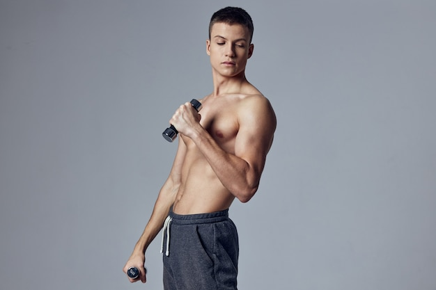 Sports guy workout exercise dumbbells in the hands of the gym
