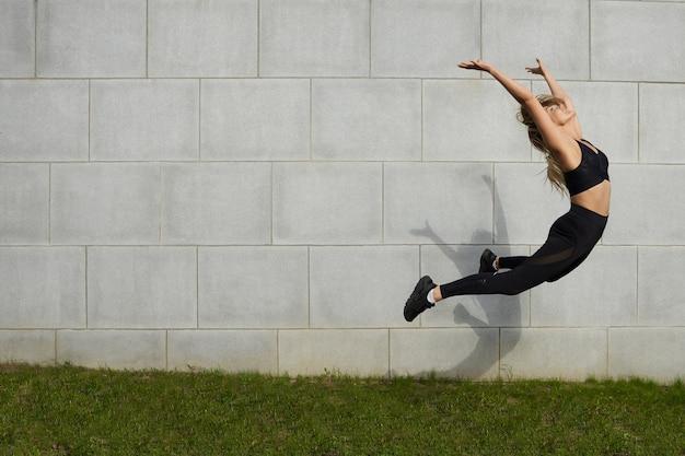 스포츠, 건강, 활동, 피트니스, 웰빙 및 여름철 개념. 야외에서 워밍업하는 동안 높은 점프 세련된 검은 옷에 아름다운 젊은 백인 운동가의 액션 샷을 고정