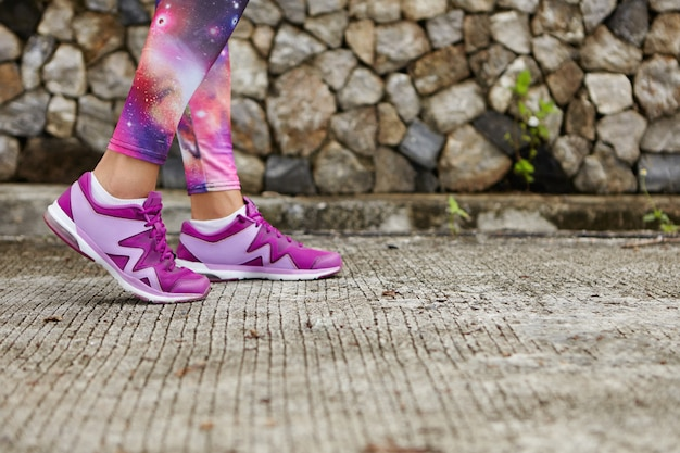 Sports and healthy lifestyle. close up of woman's legs in stylish purple sneakers and space print leggings on pavement. female athlete standing on concrete, doing physical exercises in city park