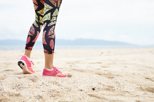 Sports and healthy lifestyle concept. cropped shot of legs of girl athlete against ocean beach.