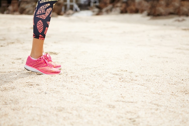 Sports and healthy lifestyle concept. side view of woman runner in pink running shoes standing on beach with copy space for your text or advertising content.