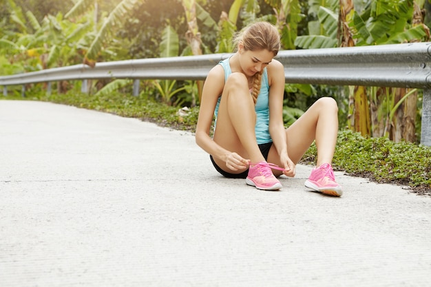 Sports and healthy lifestyle concept. young sporty girl sitting on road lacing her pink sneakers during jogging exercise outdoors.