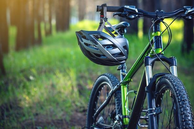 Спортивный шлем на зеленом горном велосипеде в парке. концепция защиты во время активного и здорового образа жизни