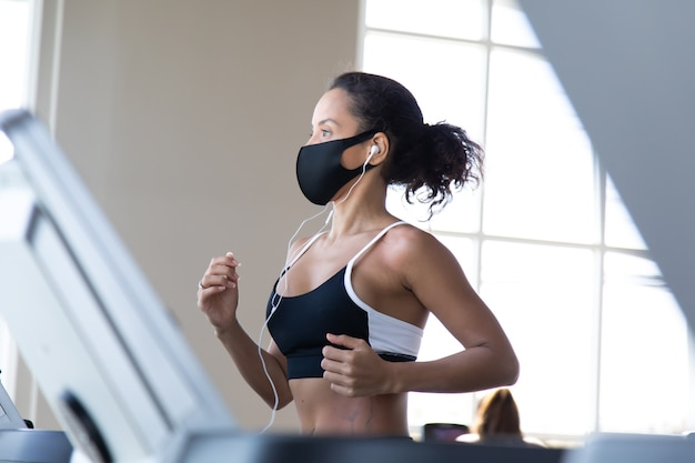スポーツヒスパニック系女性がジムのトレッドミルでトレーニングし、フェイスマスクを着用