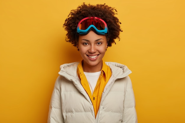 Sports holidays, travel lifestyle and winter adventure concept. glad african woman with toothy smile, snowboards in mountains, wears ski goggles and white down padded coat