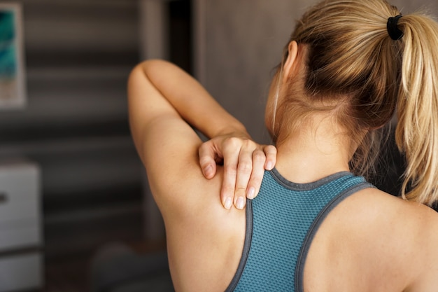 Sports injury concept. athletic girl feeling pain in her neck against blurred. pain after home workout