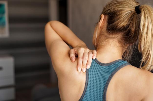Концепция спортивной травмы. спортивная (ый) девушка чувствует боль в шее против размытого. боль после домашней тренировки