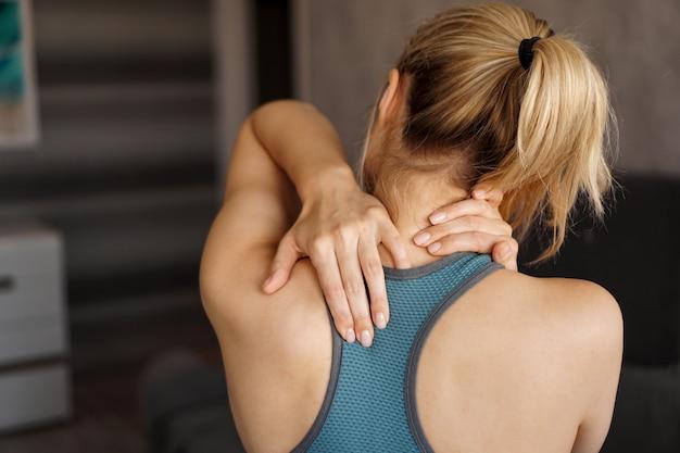 スポーツ傷害の概念。彼女の首の痛みを感じている運動の女の子。自宅でのトレーニング後の痛み