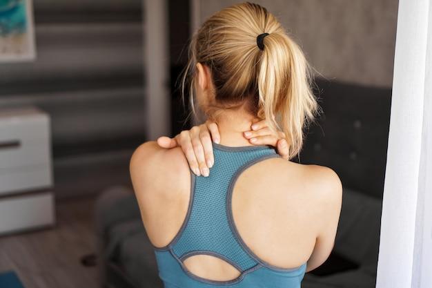Концепция спортивной травмы. спортивная (ый) девушка чувствует боль в шее. боль после домашней тренировки
