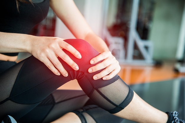 Sports injury at knee in fitness training gym. training and medical concept