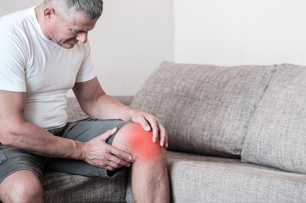 スポーツ傷害男性重量挙げ選手。耐え難いほどの痛みから膝を絞っているソファの上の男。