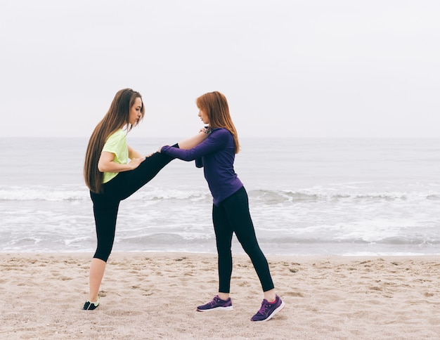Sports instructor helps the girl to do stretching on the beach