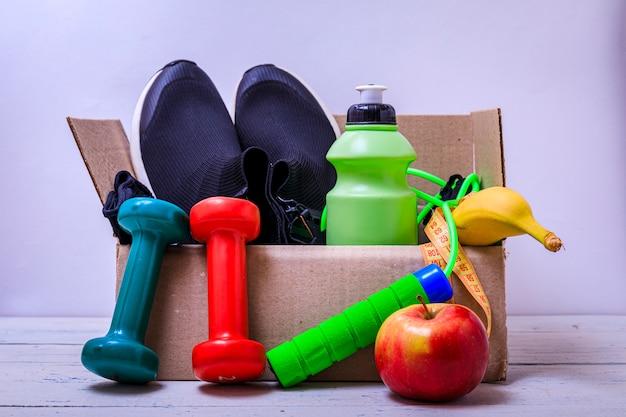 ボックスに寄付するスポーツアイテム。スポーツシューズ、リンゴ、水のボトル。チャリティー活動。