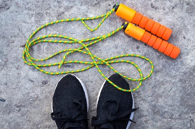 Спортивная скакалка у ног спортсмена в кроссовках
