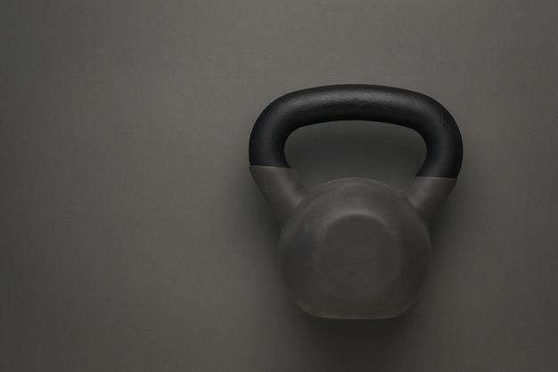 濃い灰色の背景にゴムで覆われたスポーツケトルベル。スポーツライフスタイル。