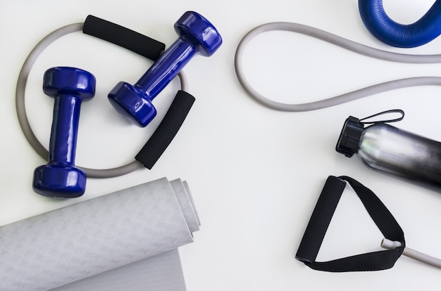 Sports kit: dumbbells, expander, yoga mat, water bottle.