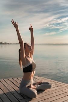 ビーチでスポーツ女性は瞑想の練習をします。