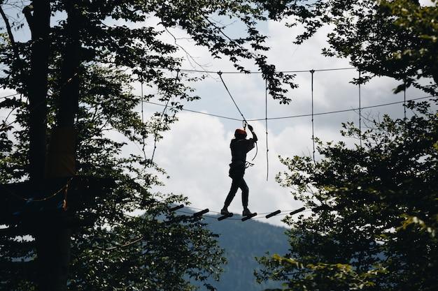 Спортивный мужской силуэт в веревочном парке в красивом лесу